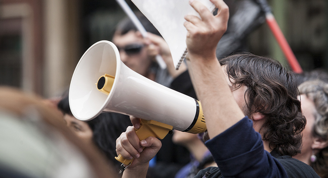 Image of a man in a group holding a megaphone.